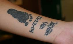 Baby footprint tattoo on forearm