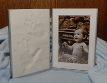 Baby footprint or handprint framed in clay